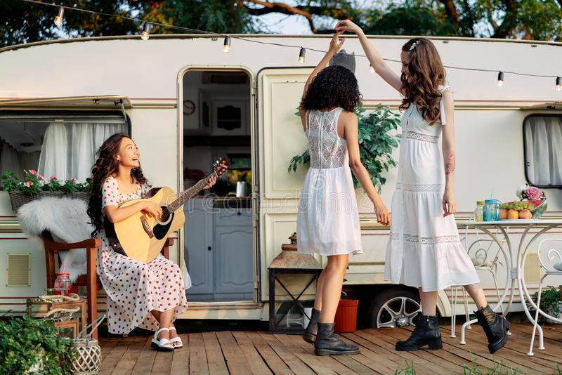 Young happy women have fun together playing guitar and dancing outdoors near their camper van stock photo