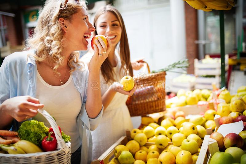 Young women shopping on the market healthy vegetables and fruits royalty free stock images