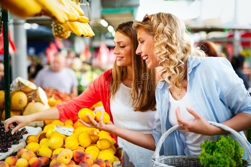 Young happy women shopping vegetables and fruits on the market royalty free stock image