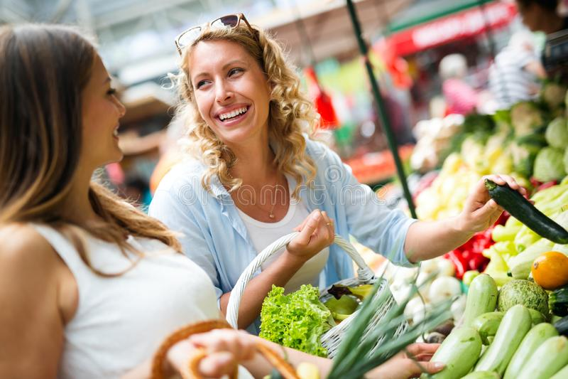 Young happy women shopping vegetables and fruits on the market royalty free stock photography