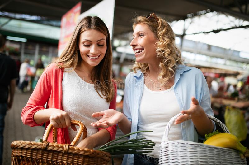Young happy women shopping vegetables and fruits on the market stock photography