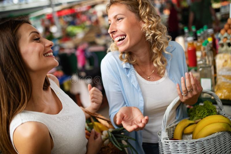 Young happy women shopping vegetables and fruits on the market stock image