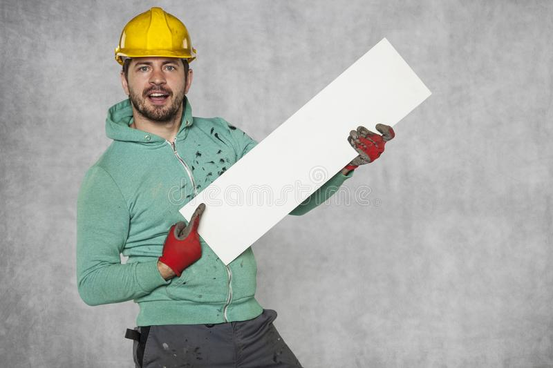 Young happy worker shows ad. Protective helmet on the head stock photos