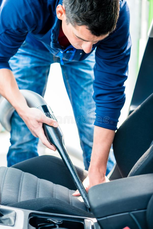 Young man using vacuum for cleaning the interior of a car. Young hard-working man using vacuum for cleaning the interior of a car at auto wash royalty free stock images
