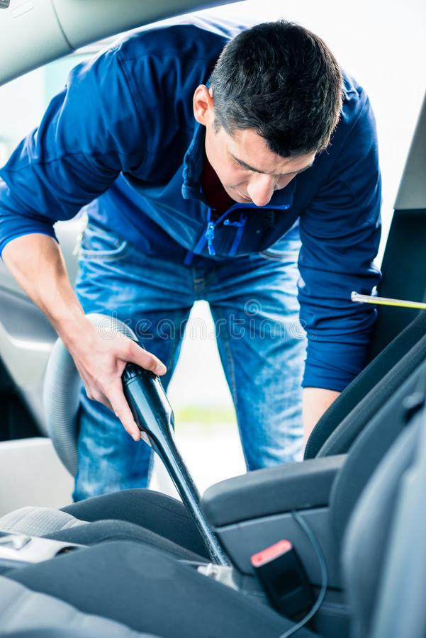 Young man using vacuum for cleaning the interior of a car. Young hard-working man using vacuum for cleaning the interior of a car at auto wash stock image