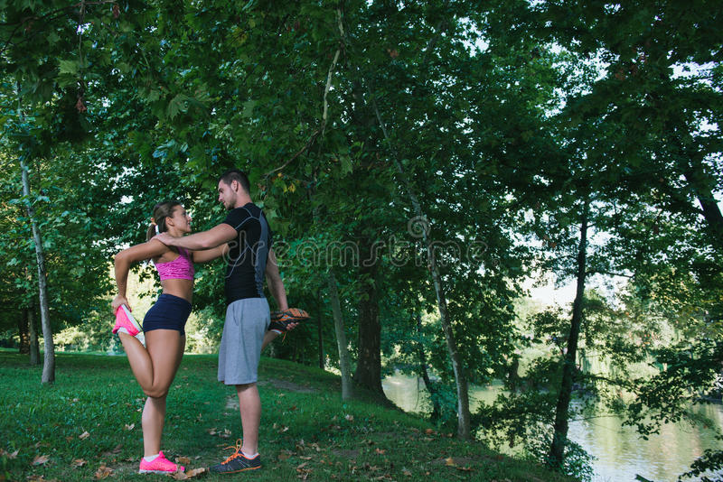 Young health couple doing stretching exercise relaxing and warm up after jogging and running in park royalty free stock images