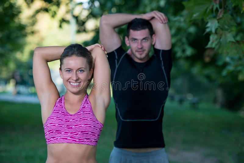 Young health couple doing stretching exercise relaxing and warm up after jogging and running in park stock photography