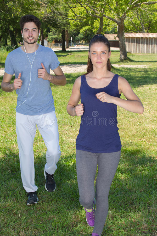Young health couple jogging in park stock photography