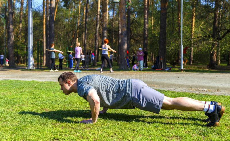 Young healthy caucasian sportsman doing push-ups on track field. Young healthy caucasian sportsman in uniform doing push-ups on track field and looking straight stock image
