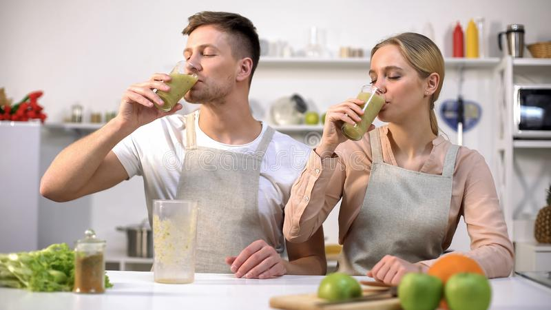 Young healthy couple drinking fresh spirulina smoothie, vitamins and minerals stock photo
