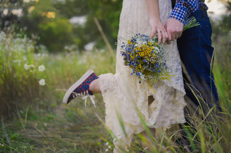 Young healthy couple fashionable girl in a wedding dress guy in a plaid shirt standing with a bouquet of bright flowers in hands,. Young healthy couple stock photo
