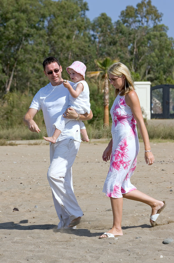 Young, healthy family walking along a sunny beach stock photo