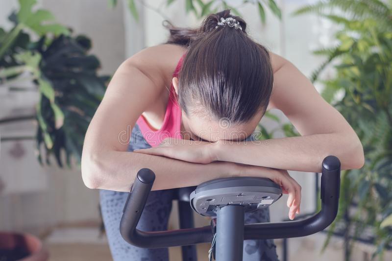 Young healthy fit woman training at home on exercise bike during work-out feeling exhausted and dizzy, lowered his head on his han royalty free stock photo