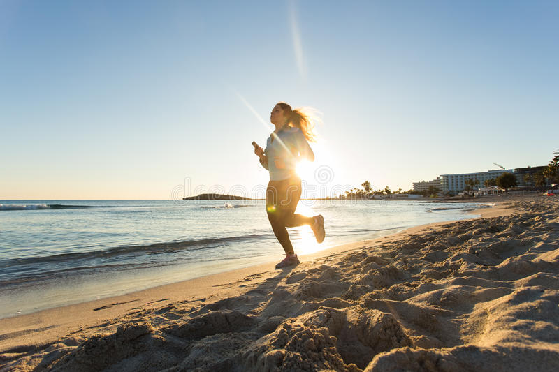 Young healthy lifestyle fitness woman running at sunrise beach stock photo