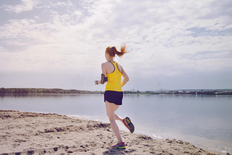 Young healthy lifestyle woman running at sunrise beach. stock photos