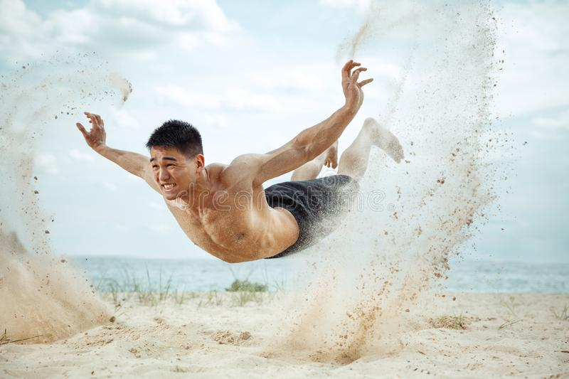 Young healthy man athlete doing squats at the beach royalty free stock photo