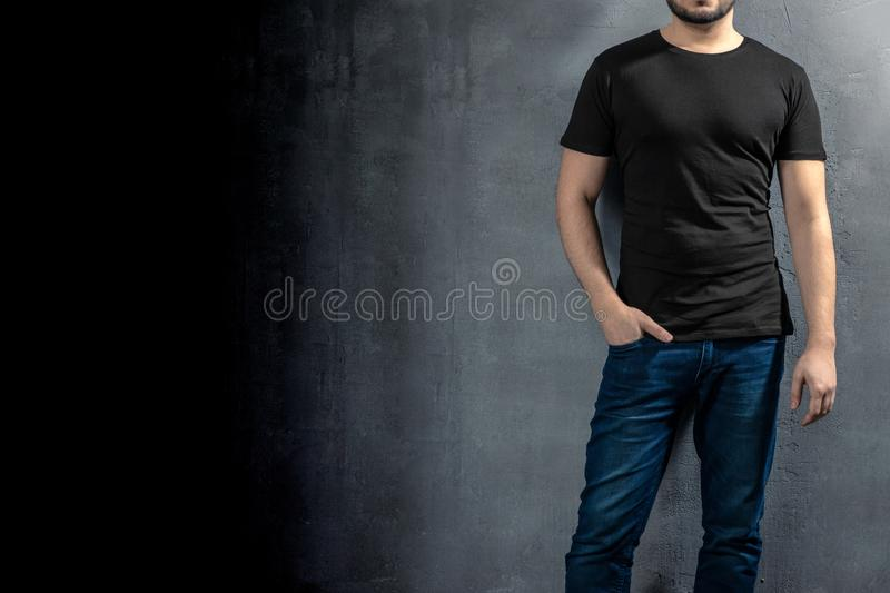 Young healthy man with black T-shirt on concrete background with copyspace for your text royalty free stock image