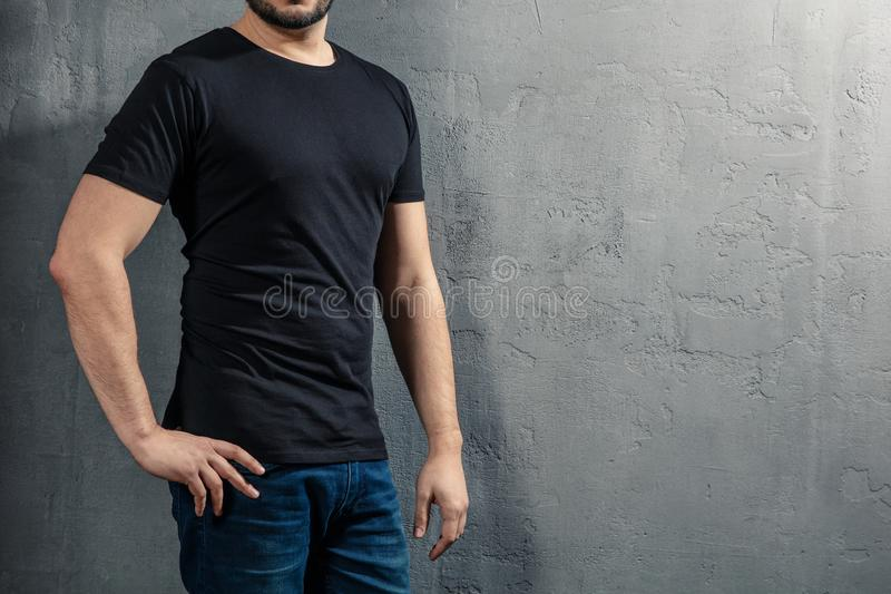 Young healthy man with black T-shirt on concrete background with copyspace for your text royalty free stock images
