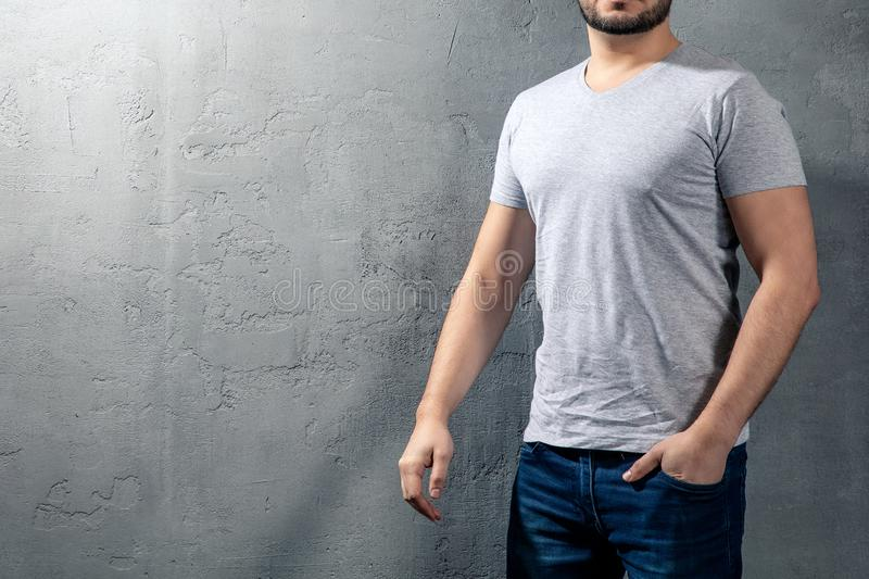 Young healthy man with grey T-shirt on concrete background with copyspace for your text stock photography