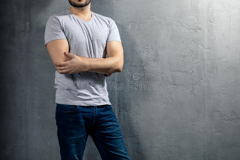 Young healthy man with grey T-shirt on concrete background with copyspace for your text royalty free stock photos