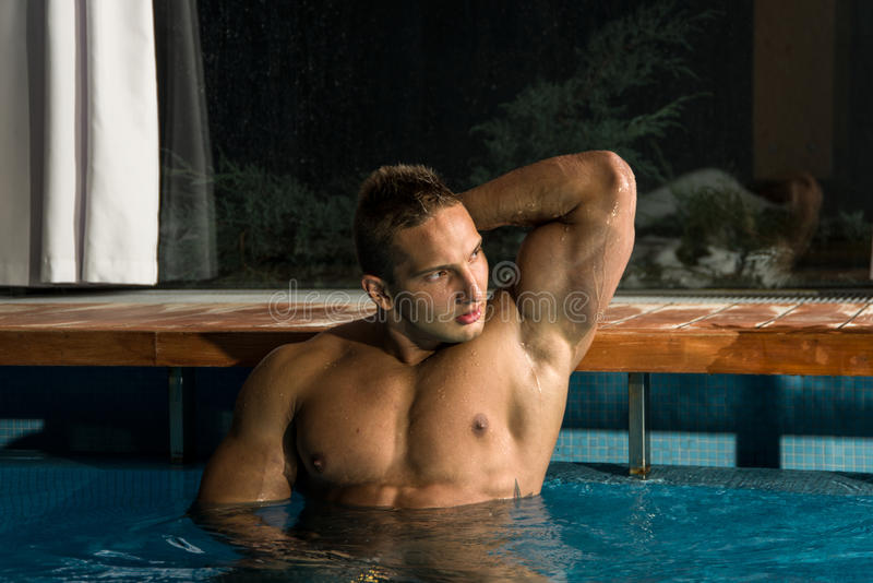 Young healthy man with muscular body. Swims in swimming pool and representing healthy and recreation concept royalty free stock image
