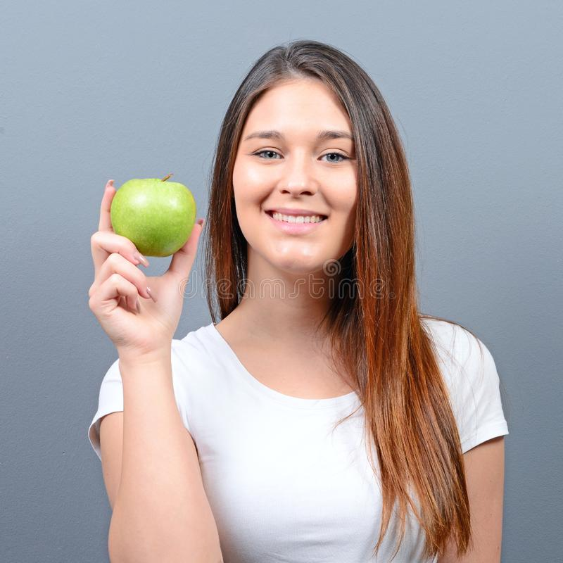 Young healthy woman holding green juicy apple against gray background royalty free stock photography