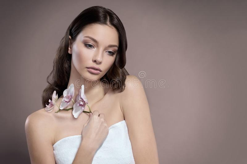 Young and healthy woman with light make-up is holding the Orchid flower. Beige background. stock photos