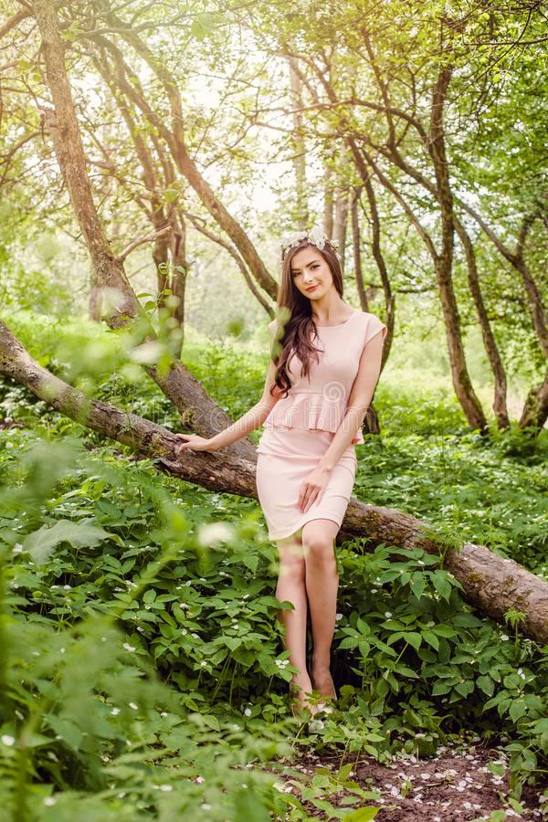 Young healthy woman outdoors portrait. Beauty girl in flowers wreath in blossom garden in sunny spring day stock photography