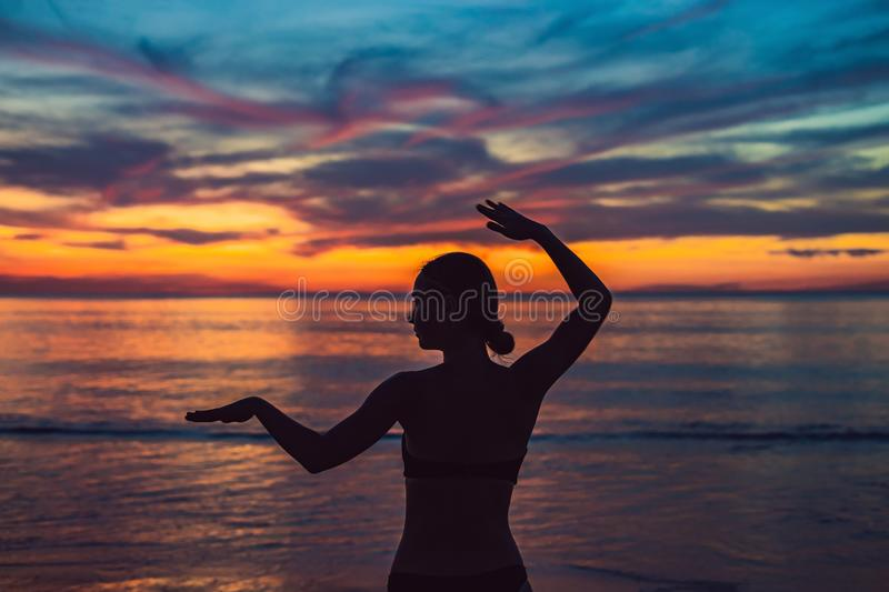 Young healthy woman practicing yoga on the beach at sunrise, benefits of natural environments for physical royalty free stock images