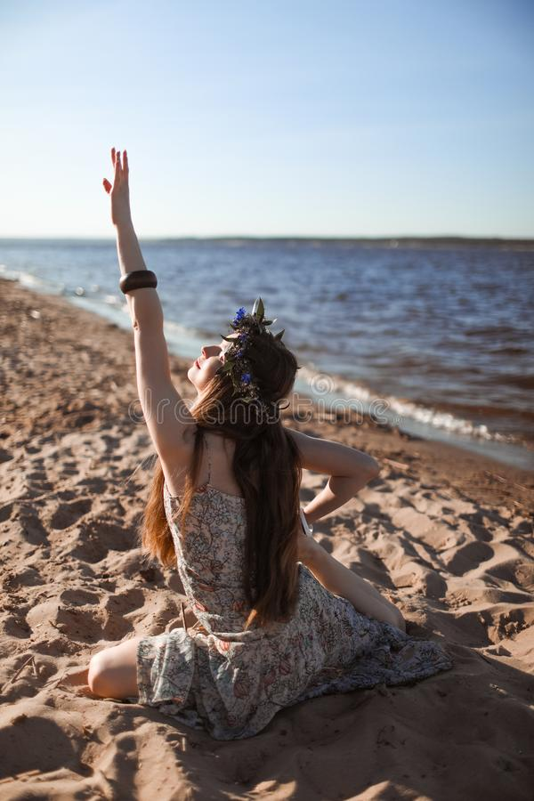 Young healthy woman practicing yoga on the beach at sunrise. royalty free stock photo