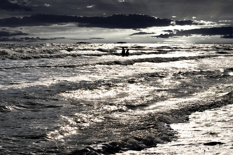 Young at heart seniors in sea. Two seniors in storming waves of the sea on a background dramatic sunset sky royalty free stock photography