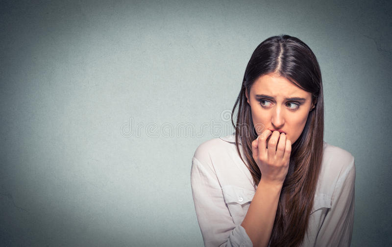 Young hesitant nervous woman biting fingernails craving or anxious. Young hesitant nervous woman biting her fingernails craving something or anxious, on gray stock photo