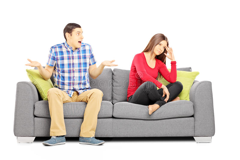 Young heterosexual couple sitting on a couch during an argument. Isolated on white background stock images
