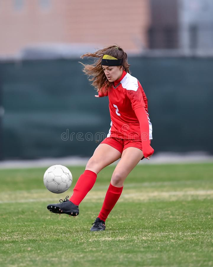 Young high school girl competing in a soccer game royalty free stock image