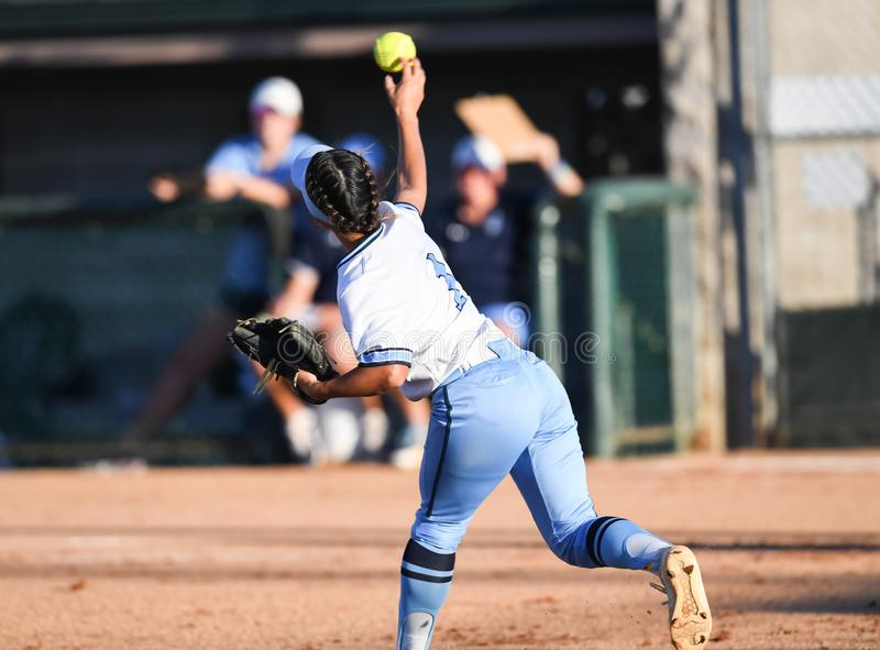 Young high school softball players in action, making amazing plays, during a game. Teen high school girls playing fast-pitch softball. Amazing plays and action royalty free stock photography
