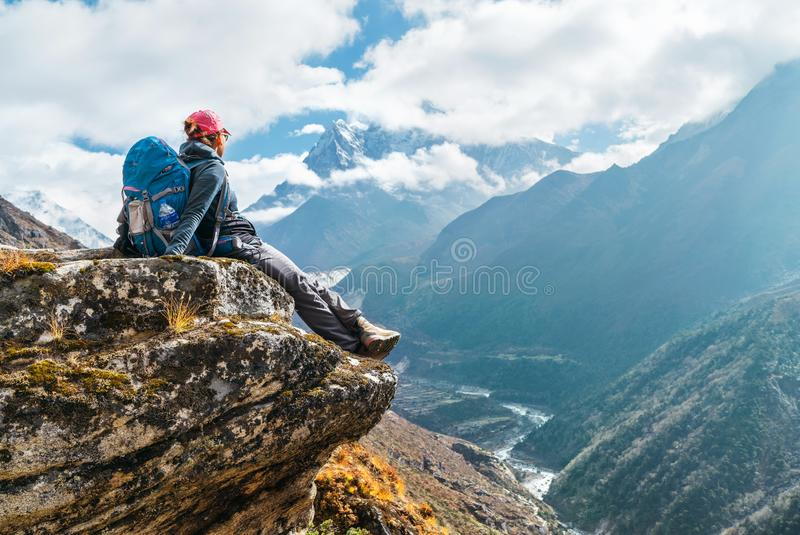 Young hiker backpacker female sitting on the cliff edge and enjoying Ama Dablam 6,812m peak view during Everest Base Camp EBC royalty free stock photography