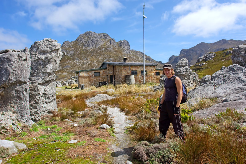 Young hiker and chalet. Young hiker stands in front of mountain chalet. Shot in Hottentots-Holland Mountains nature reserve, near Grabouw, Western Cape, South royalty free stock images
