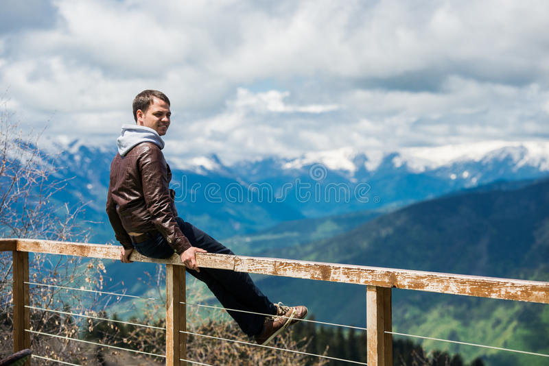 Young hiker on cliff`s edge and looking to mountains.  stock photo