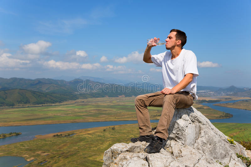 Young hiker drinks water on top of the mountain royalty free stock photo