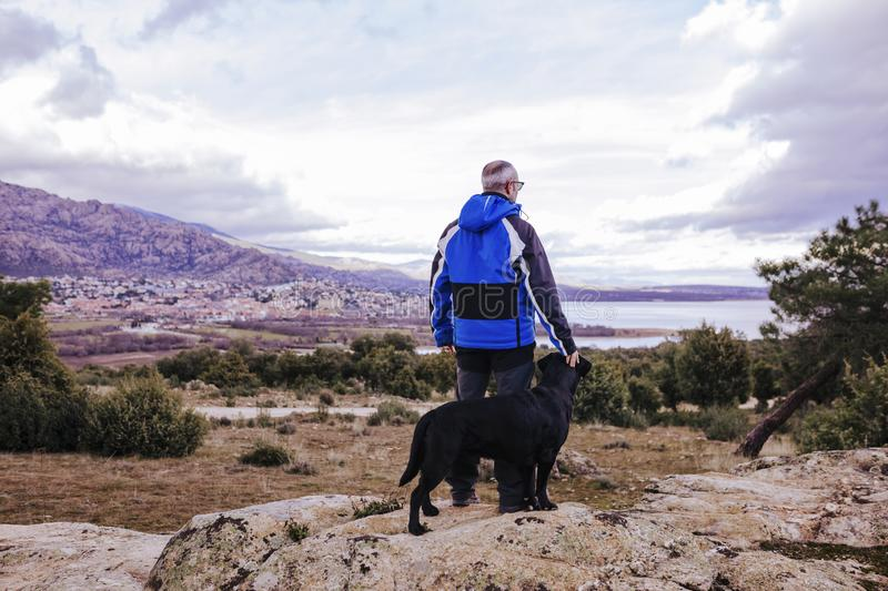 young hiker man at the mountain with his black labrador on top of a rock. cloudy winter day. back view stock images