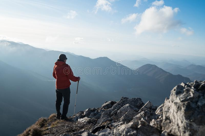 Young hiker Man standing with trekking poles on cliff edge and looking at Tatra mountains valley. Successful summit concept image. stock image