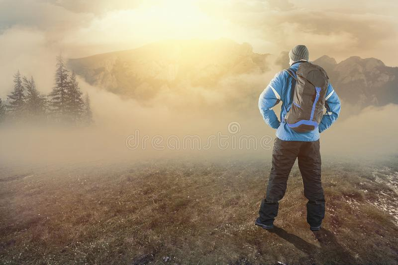 Young hiker on the mountains. At sunrise on a foggy day stock photos