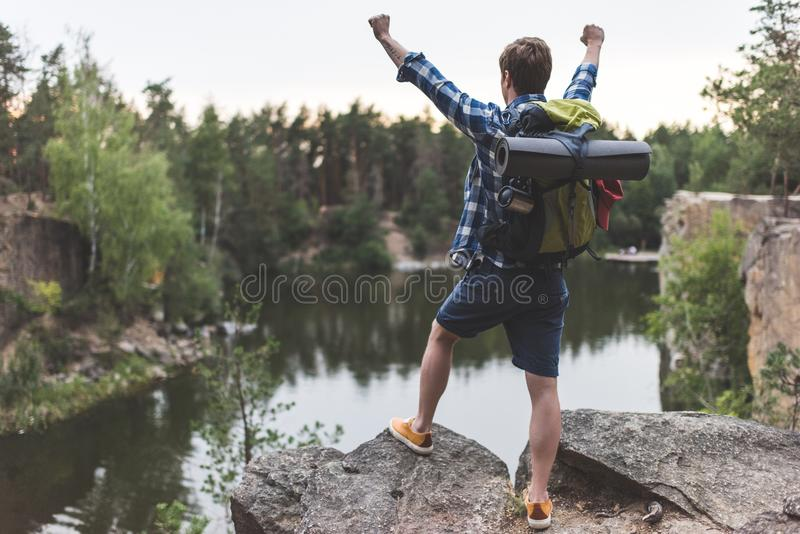 young hiker raising fists while looking royalty free stock image