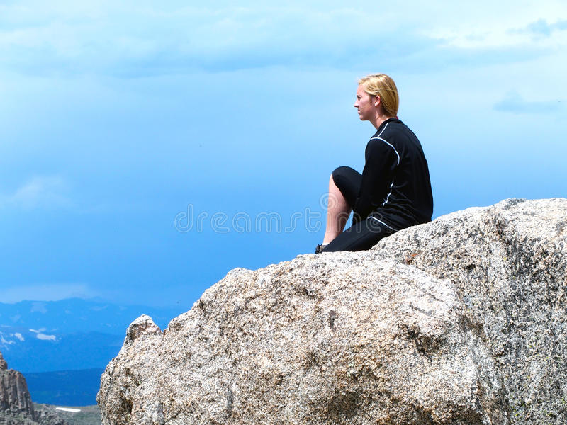 Young Hiker Sitting on a Rock. Young woman hiker sitting on a large granite rock gazing over the mountains near Summit Lake on Mount Evans in the Colorado stock photo