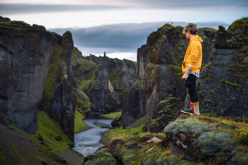 Young hiker standing at the edge of the Fjadrargljufur Canyon in Iceland stock photo
