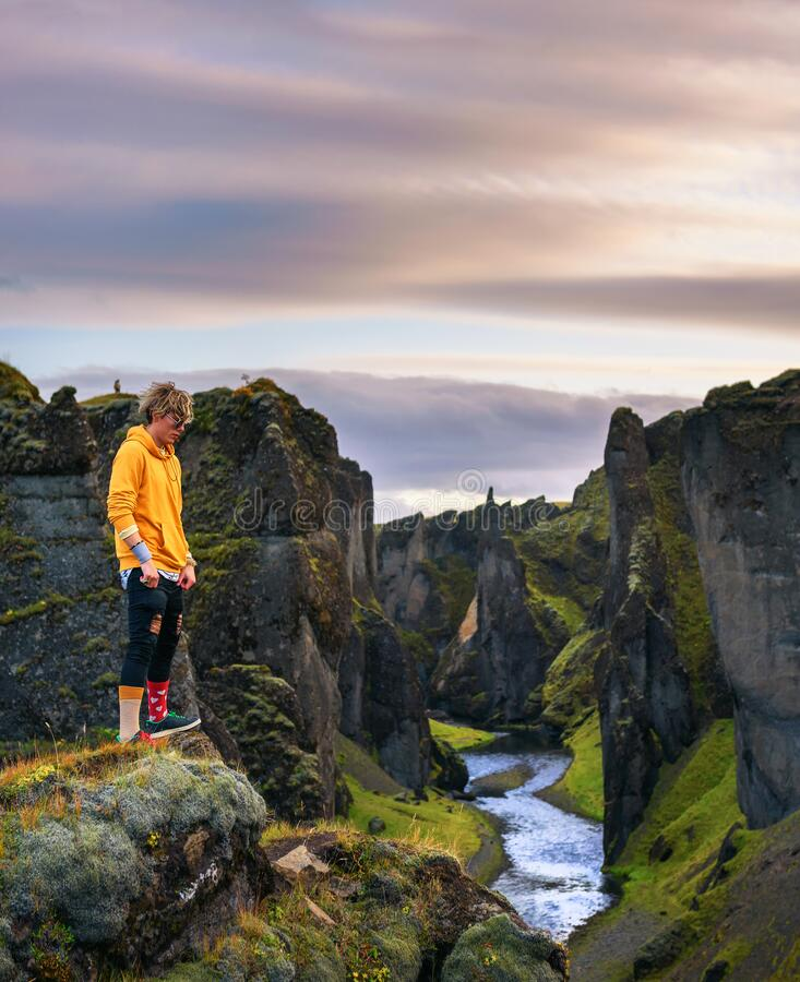 Young hiker standing at the edge of the Fjadrargljufur Canyon in Iceland royalty free stock photos