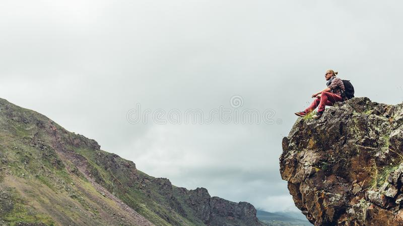 Young hiker traveler man sitting on top and enjoy view of mountain summer spring valley, copy-space. Adventure wanderlust stock images