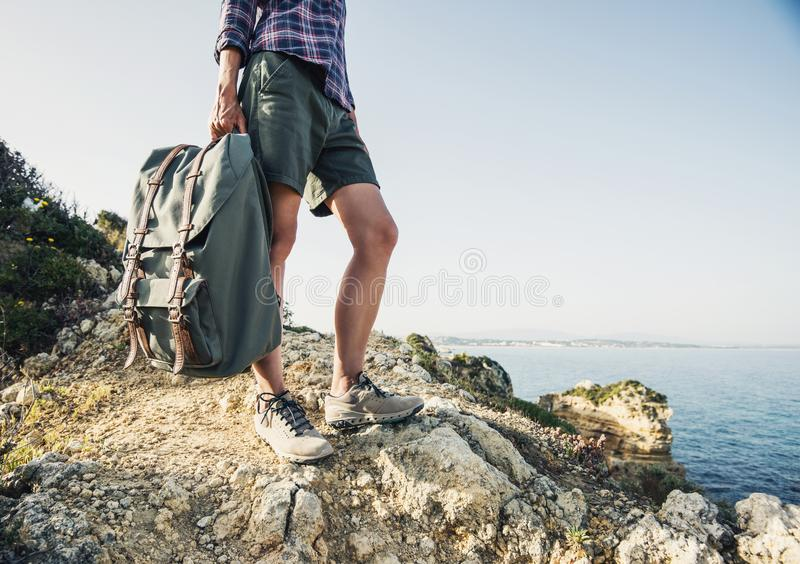 Young traveler woman holding backpack on a hiking trail, travel and active lifestyle concept stock image