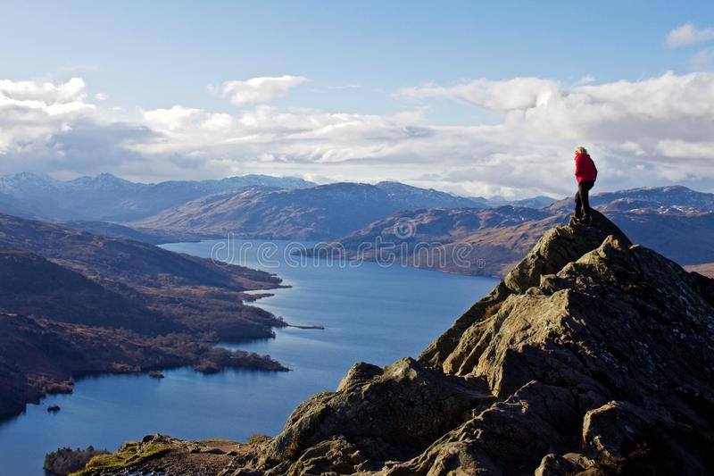 Young Hiker Woman on Top of Mountain Looking at Lake stock photography