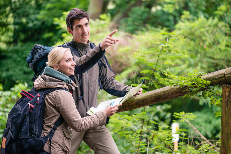 Young hikers orientating with trail map royalty free stock photography
